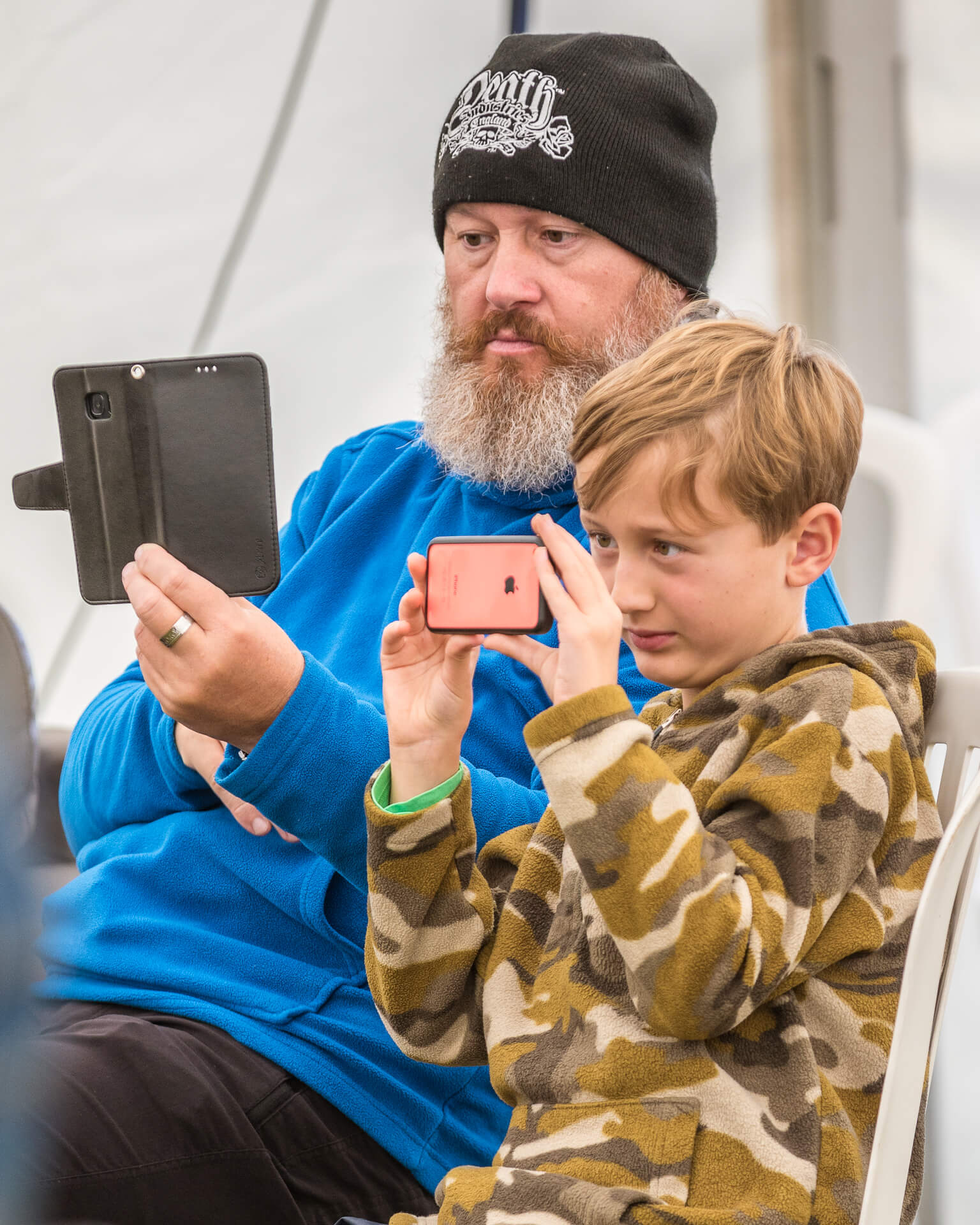 Seen in colour this waist up image of (what appears to be) a Father and his young Son as they sit side by side, both staring their phones at the same time. Taken at the Dubs of Anarchy Festival in 2019.