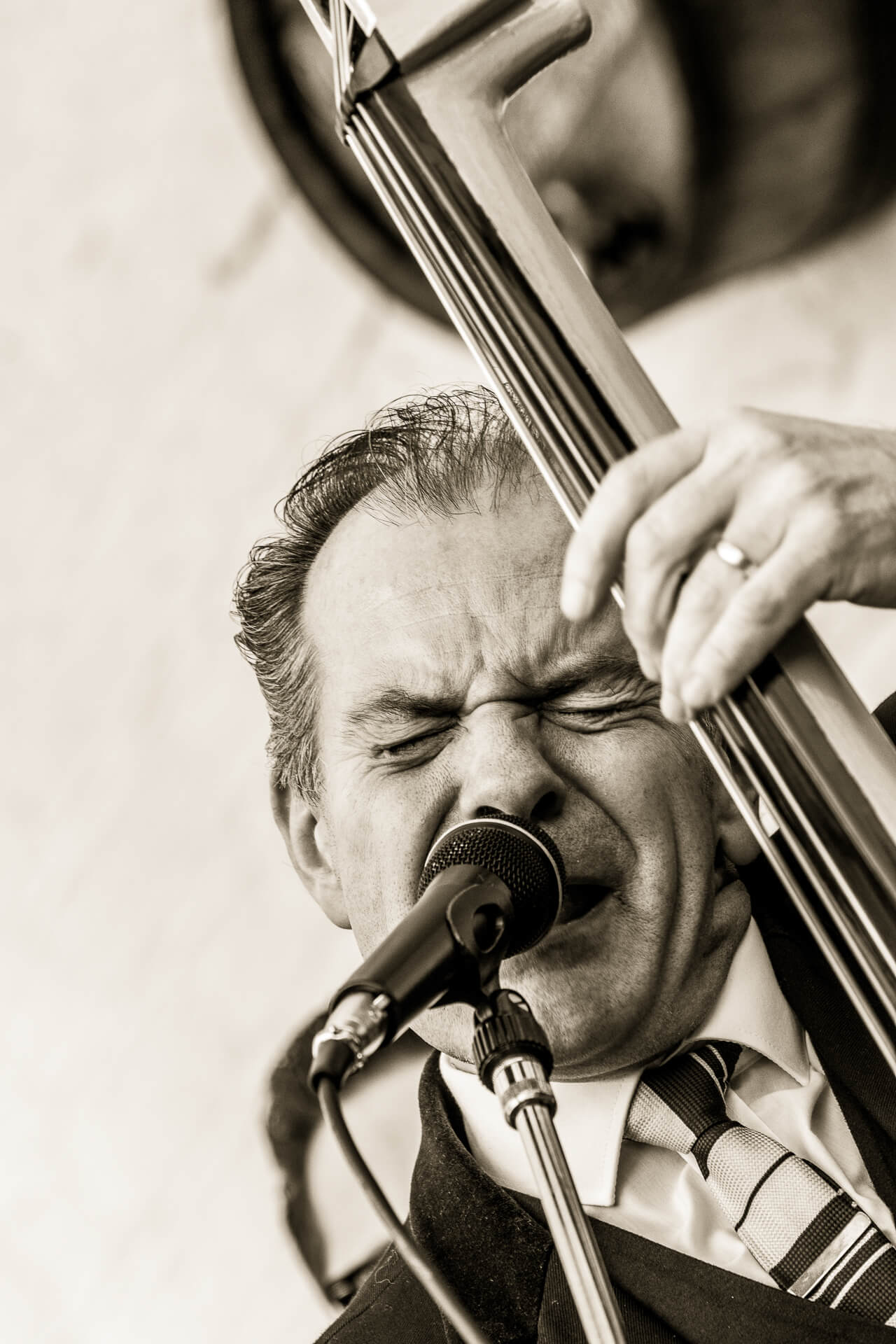 A head and shoulders shot of Martin, lead singer and double bass player of the UK Fireballs singing during a performance at the Worcester Music Festival 2018