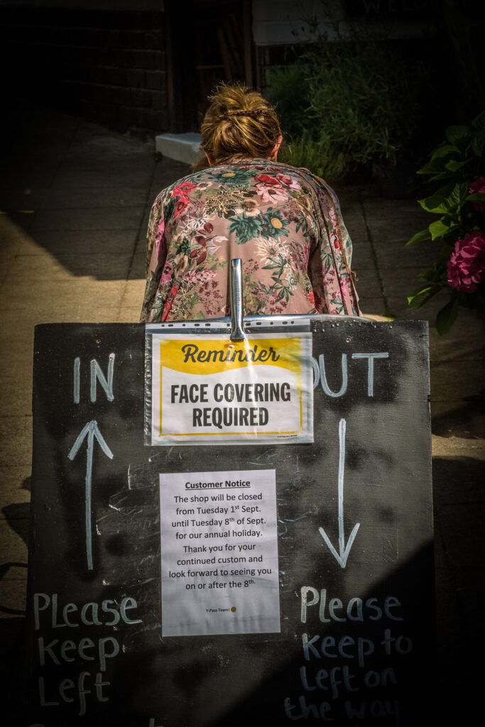 A colour view of part of a 'Reminder' sign out side of The Y Pass Fish & Chip Shop in Ledbury reminding people to wear face coverings when entering the premises. Sat behind the sign is Sara in a flowery lightweight top.