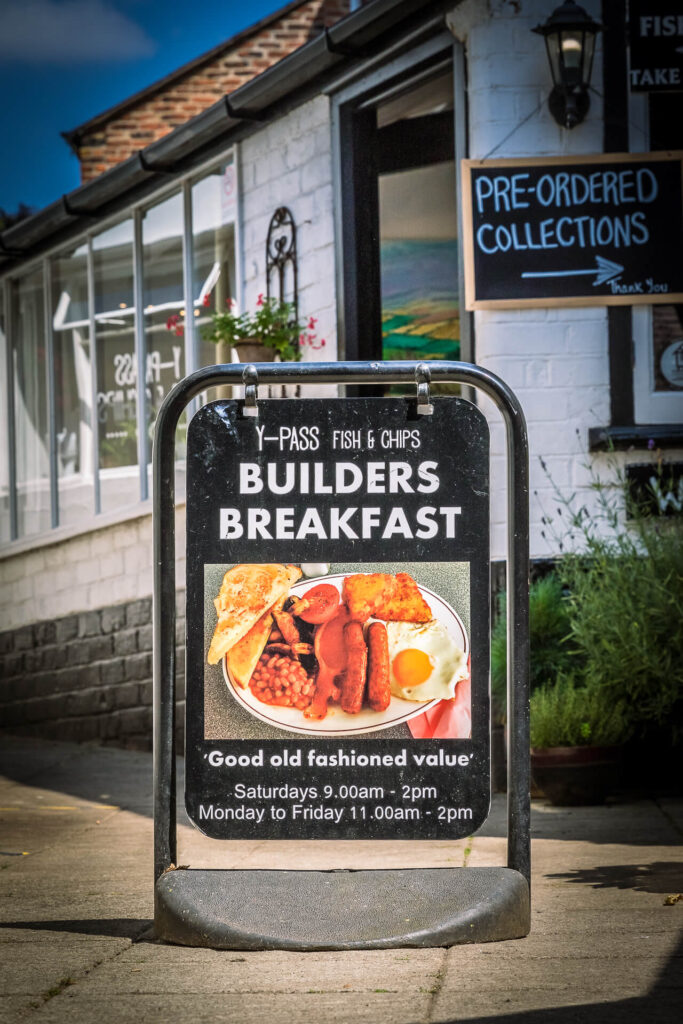 """A colour image of a free standing sign outside the Y-Pass Fish & Chip Shop in Ledbury advertising its 'Builders Breakfast'. There is a picture on the sign of a full fry up, under the picture are the words """"Good Old Fashioned Value""""."""