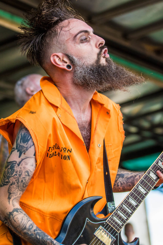 'Mawgster' of the Cheltenham based band Isolation is seen here (in colour) playing his guitar whilst on stage with the band at The Drunken Monkey Rock Festival. The festival is held in Upton Upon Severn annually to raise funds to support The Midlands Air Ambulance. Taken as Mawgster who is dressed in a bright orange sleeveless ripped 'jump suit' and is sporting a curly beard looks out to the crowd!