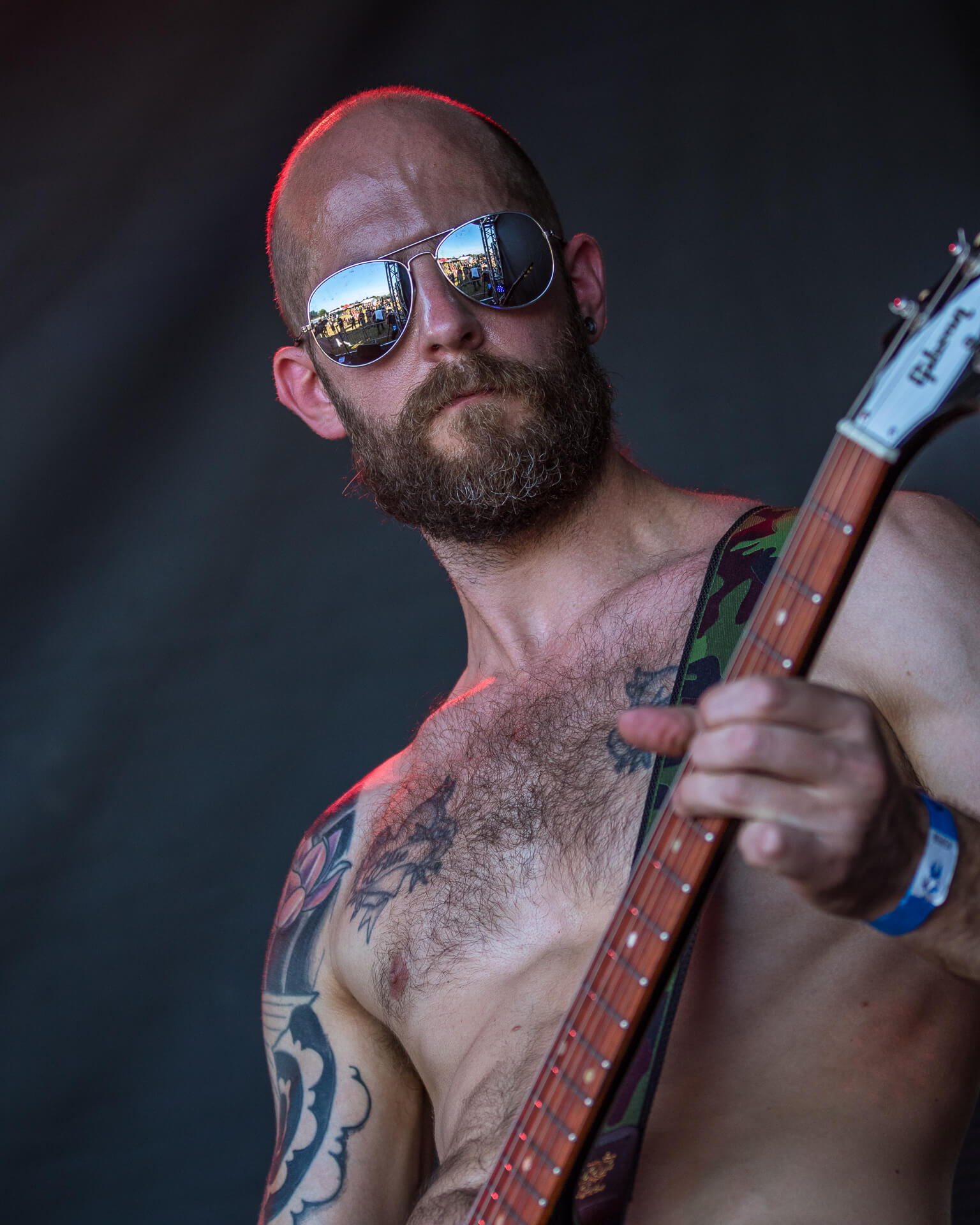 A colour image (taken from the waist upwards) of a bare chested Clive. Clive plays guitar on stage with the band Broodmother at The Drunken Monkey Rock Festival 2019.
