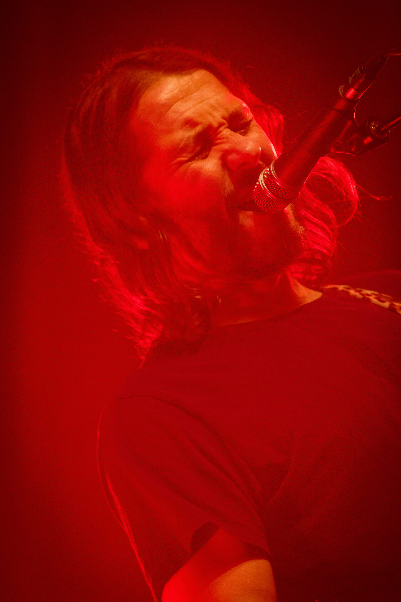 A red tinged close up photograph of Feeder lead singer Grant Nicholas singing at Lakefest 2017.