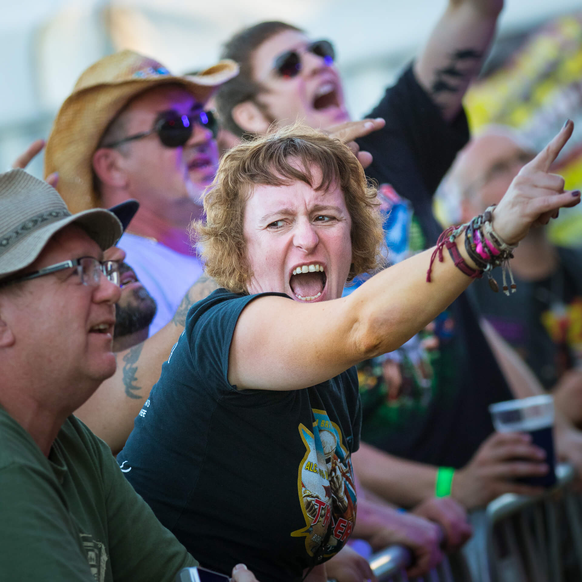 A chest up colour image of my good friend Vicky at the Drunken Monkey Rock Festival 2019. She is seen here at the barrier as she gets in the mood. She is open mouthed (probably screaming) and she holds her right arm up giving the 'Horns' sign whilst looking to her right, where Dave, her husband, stands arms folded and leaning on the barrier watching the band on stage.