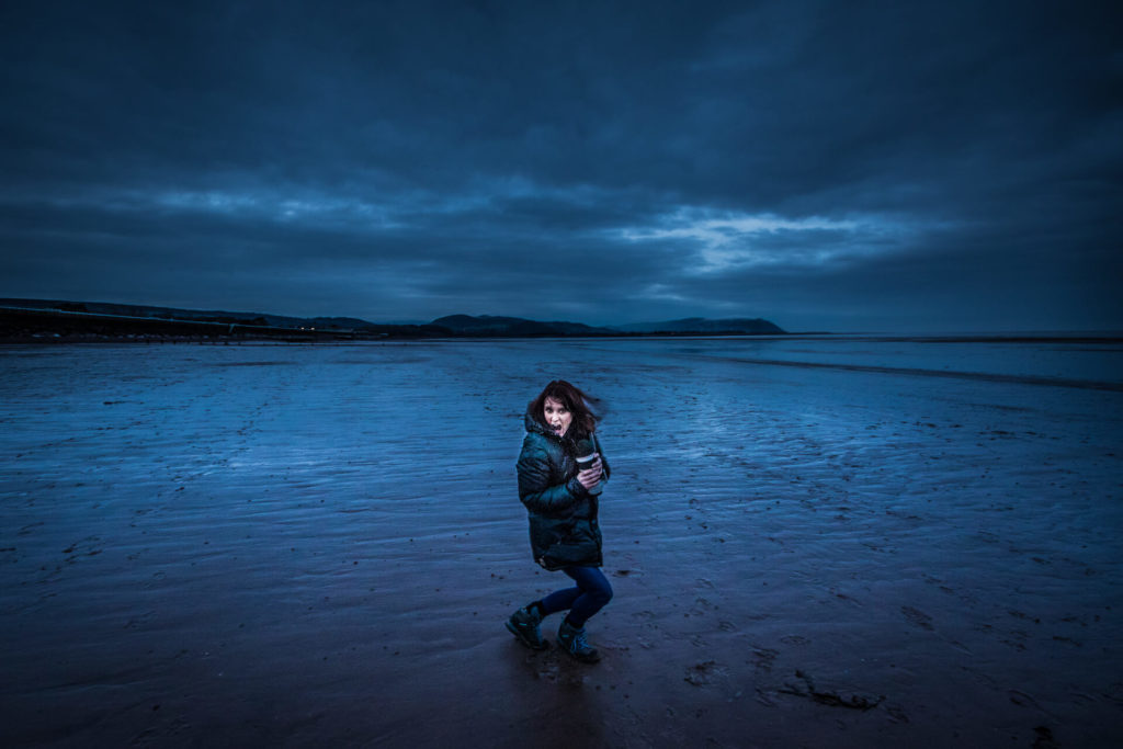A colour image (with a blue tinge) of Sara as she stands knees bent, long lens in hand, looking back at the camera whilst on a long sandy Somerset beach at dusk. There is a layer of stratus cloud over the whole area.