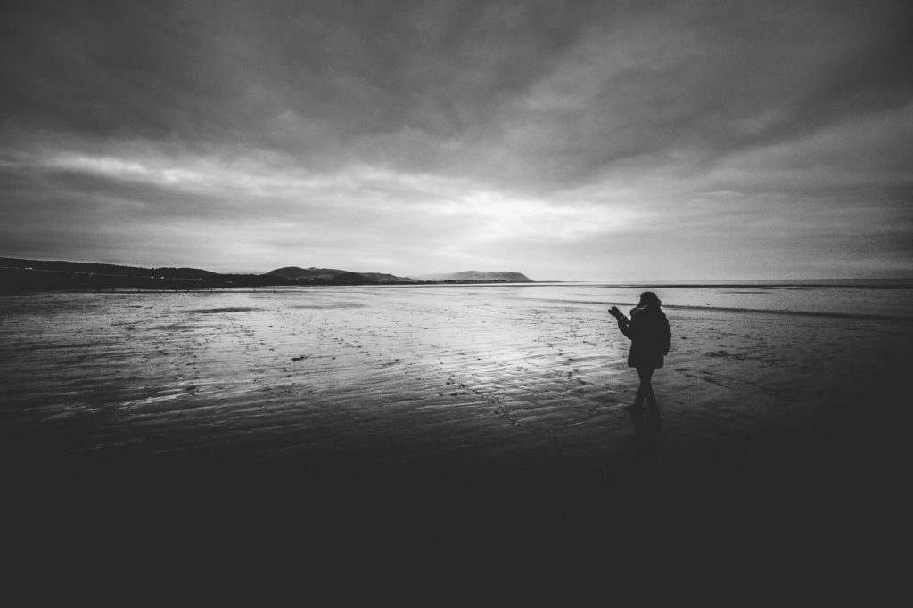 A black & white image of Sara as she stands, camera in hand, looking out along a long sandy Welsh beach at sunset. There is a layer of stratus cloud over the whole area.