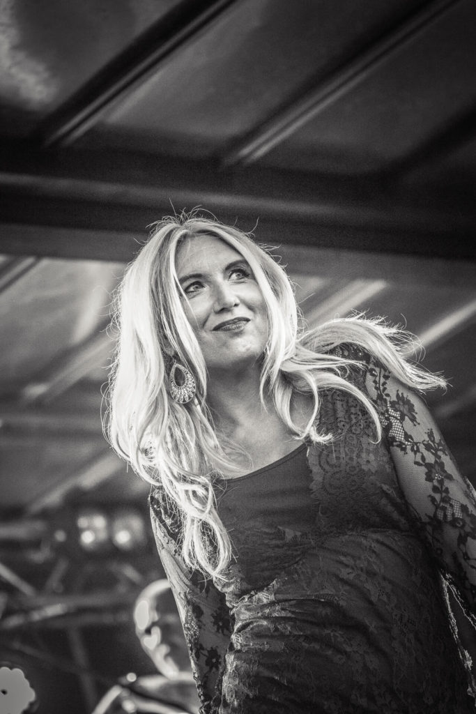A waist up black and white image of a long blonde haired female performer at The Drunken Monkey Rock Festival. She smiles as she looks out into the audience.
