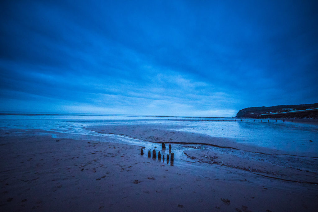 A blue tinged coloured image of a deserted sandy beach at sunset where the tide is ebbing. There are several small rotting groynes in the foreground.