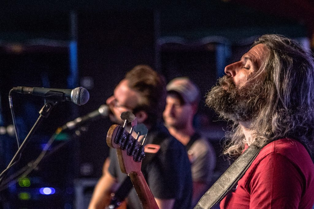 Eddie Myer (Bassist with Turin Breaks) gets lost in the moment whilst on stage at Lakefest 2017. In the background are Olly Knights (lead singer) and wearing a cap guitarist Gale Paridjanian