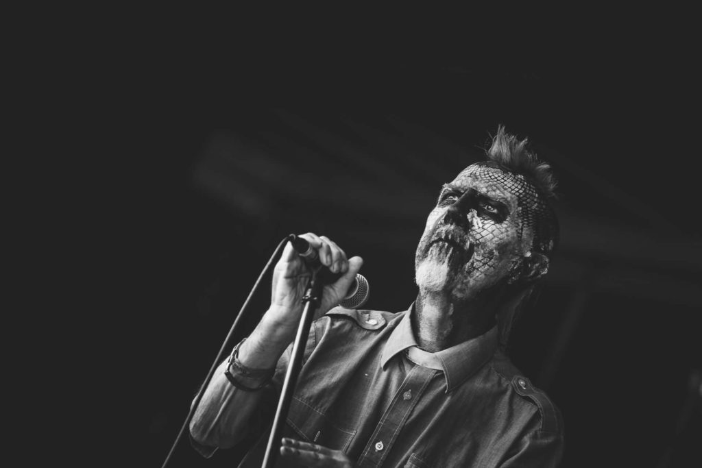 A black and white (chest up) image of Gary Lewis aka The Reverend Genghis Memphis whilst performing on stage at The Drunken Monkey Rock Festival in 2019. Gary (who passed in 2019) was frontman of the Malvern based band Massive Head Trauma. 'The Rev' is seen here holding his mic and stand in his stage make-up which consists of a white face with red and black smeared markings, and his blue Mohican haircut.