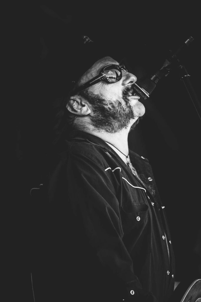 A side on black & white image of Rob Campbell, taken from the waist up, a 'Lemmy' lookalike as he performs on stage at The Drunken Monkey Rock Festival in 2019 with the band Motorheadache. Rob is seen in a typical Lemmy pose, head back and mouth close to the mic.