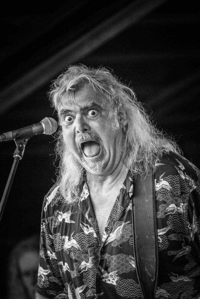 Kev, of the band Tytan, seen in black & white, and in a waist up shot on the Ian Downton stage at The Drunken Monkey Rock Festival.  Kev (formerly of the band Angel Witch) is the bassist for the band, he is seen here puling a face after noticing the camera.