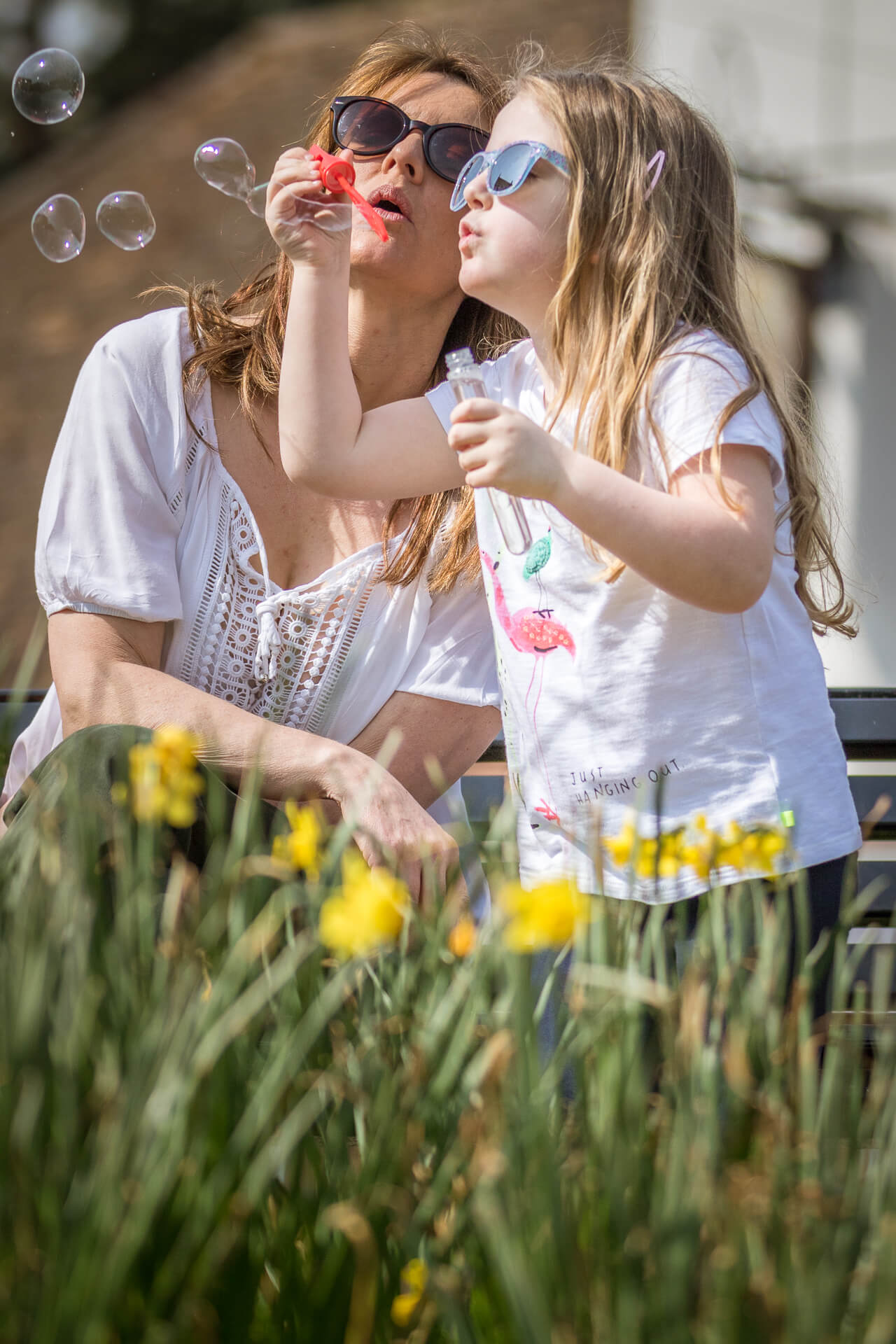 A colour view of Sara along with her friends daughter taken (in the sun) as they blow bubbles with a blower & a test tube. Sara kneels by the little one's side, both wear sunglasses.