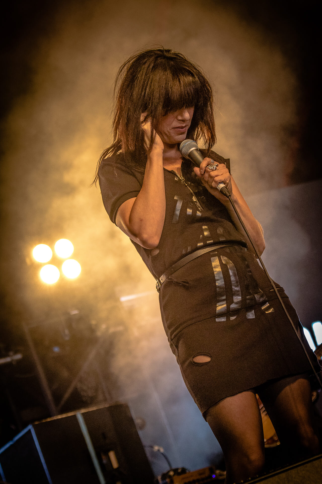 A colour 3/4 length body shot photograph, taken at Lakefest 2017, of Imelda May (in a ripped short black dress) adjusting her ear piece whilst on stage.