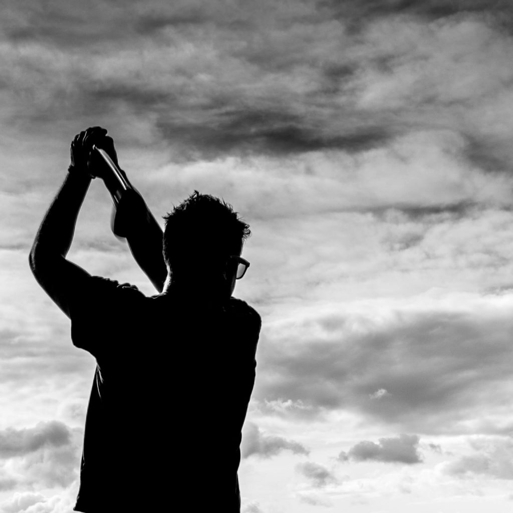 A waist up black & white image of 'Matt' as he completes a golf swing. Matt is seen in silhouette letting off steam on the morning of his wedding.