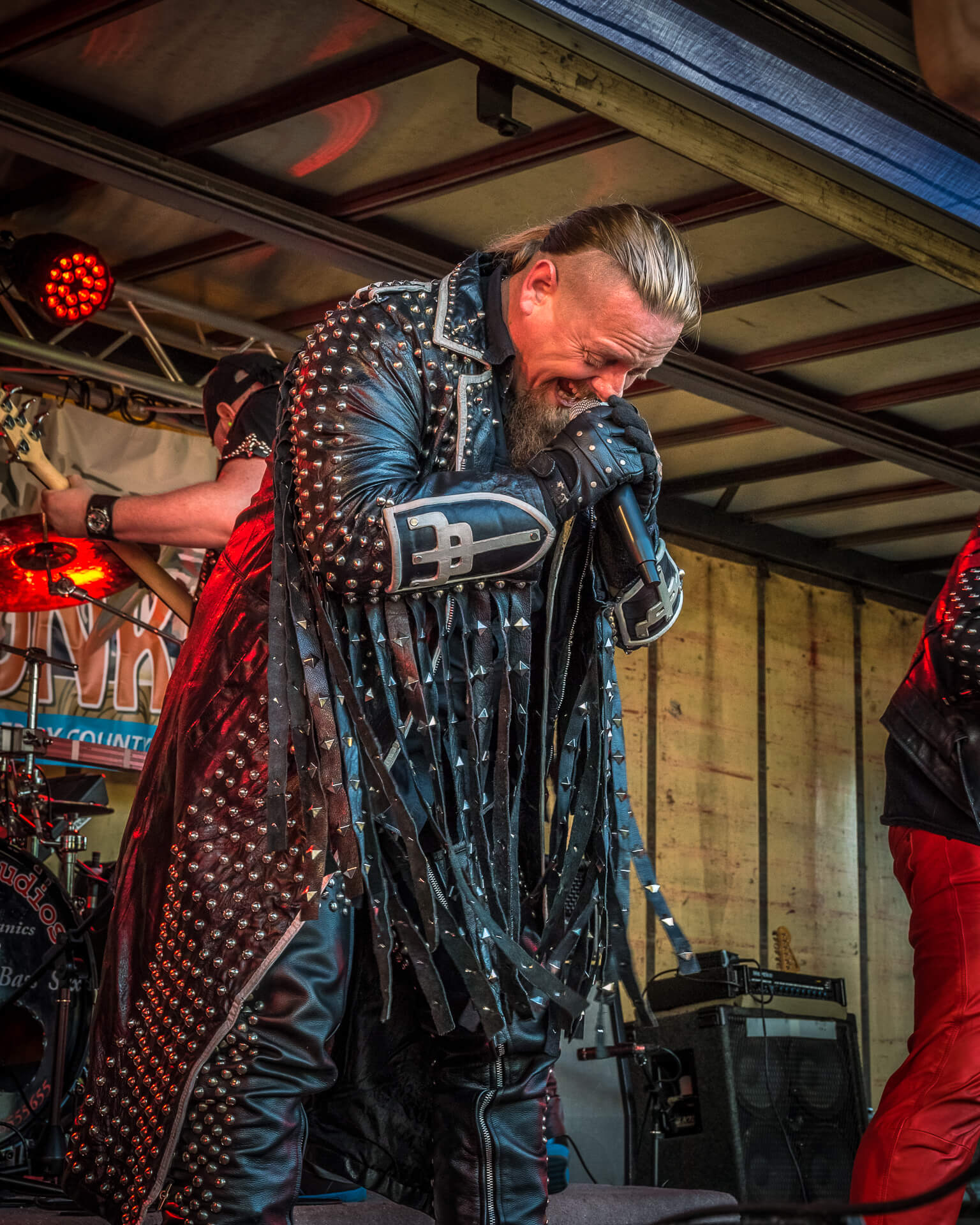 An image of Wilf, frontman of Hellbent Forever, a Judas Priest tribute band seen here on stage at The Drunken Monkey Rock Festival. This colour image shows Wilf, crouched over, as he holds the mic close to his mouth during the final part of the song. He wears his full length studded and tasseled leather coat.