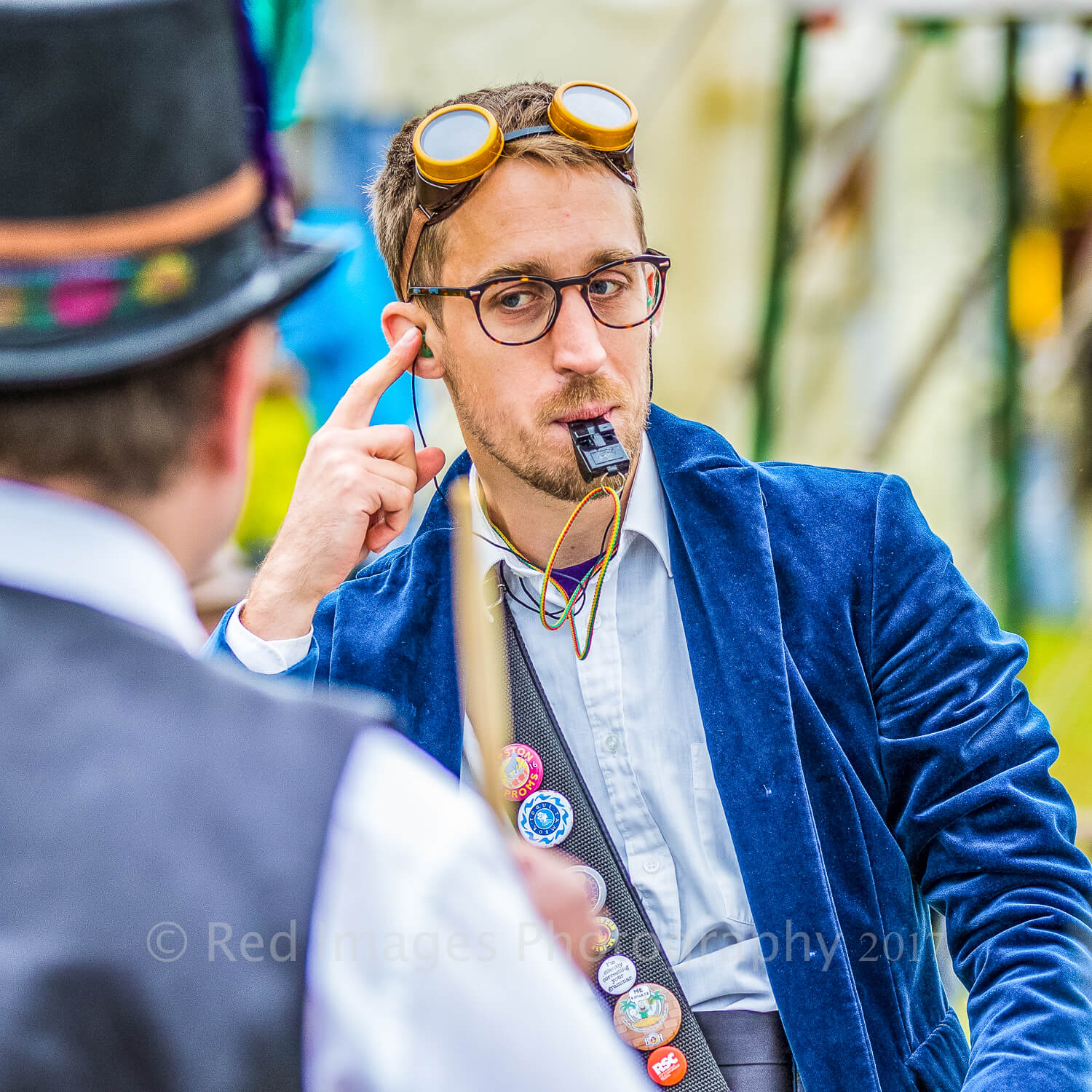 A colour waist up image of the glasses wearing conductor of a drum band playing at The Bromyard Folk Festival 2017. He wears a blue velvet jacket over a white open neck shirt, there are steam punk goggles sat on the top of his head, and has a whistle in his mouth.