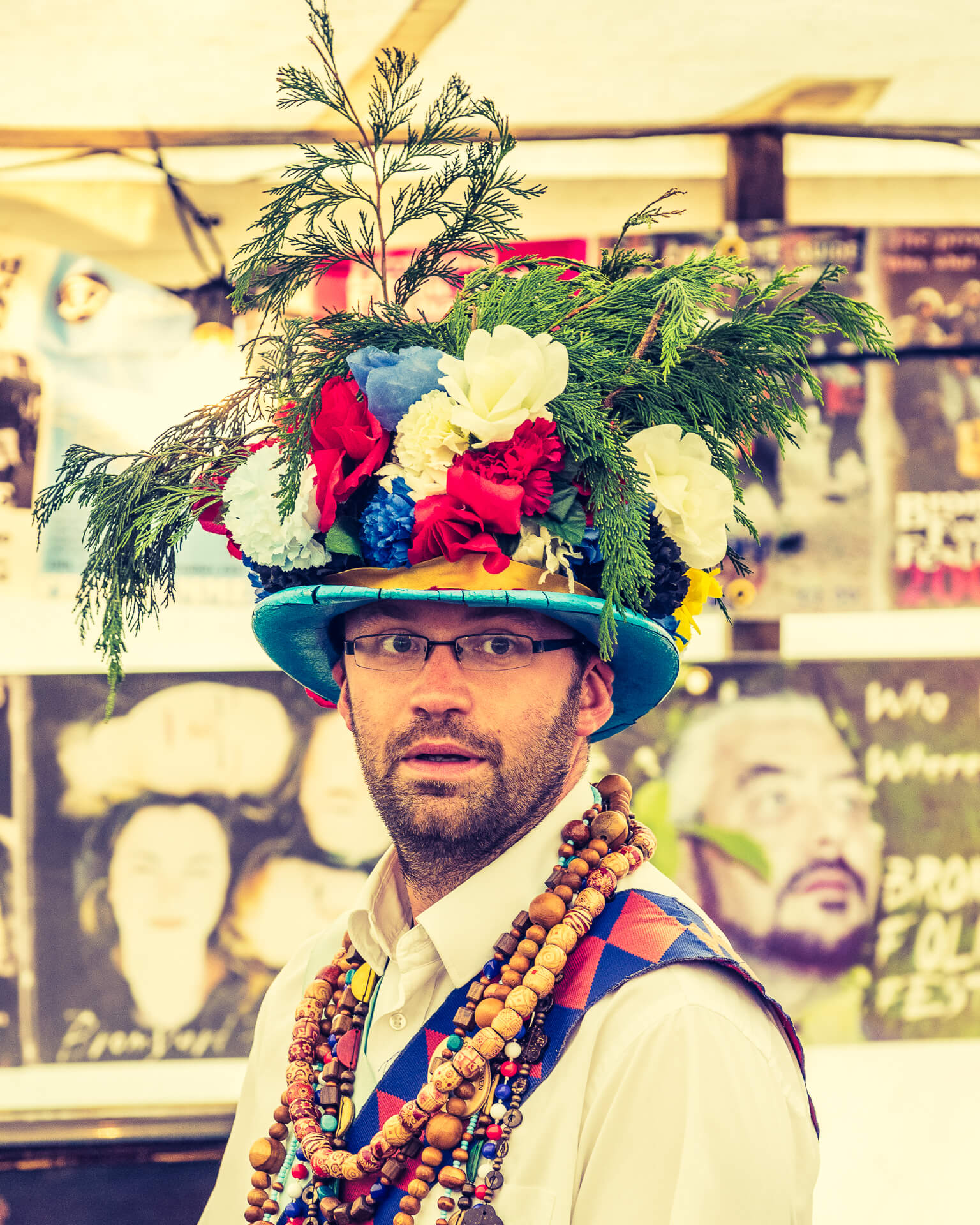 A head & shoulders image of a glasses wearing, bearded member of the Earlsdon Morris Men at the Bromyard Folk Festival in 2018. Seen in a chest up shot he wears a multicoloured multi-foilage festooned hat, along with a red and blue diamond patterned waist coat over a white shirt, and around his neck are several bead type necklaces consisting of various sized wooden beads.