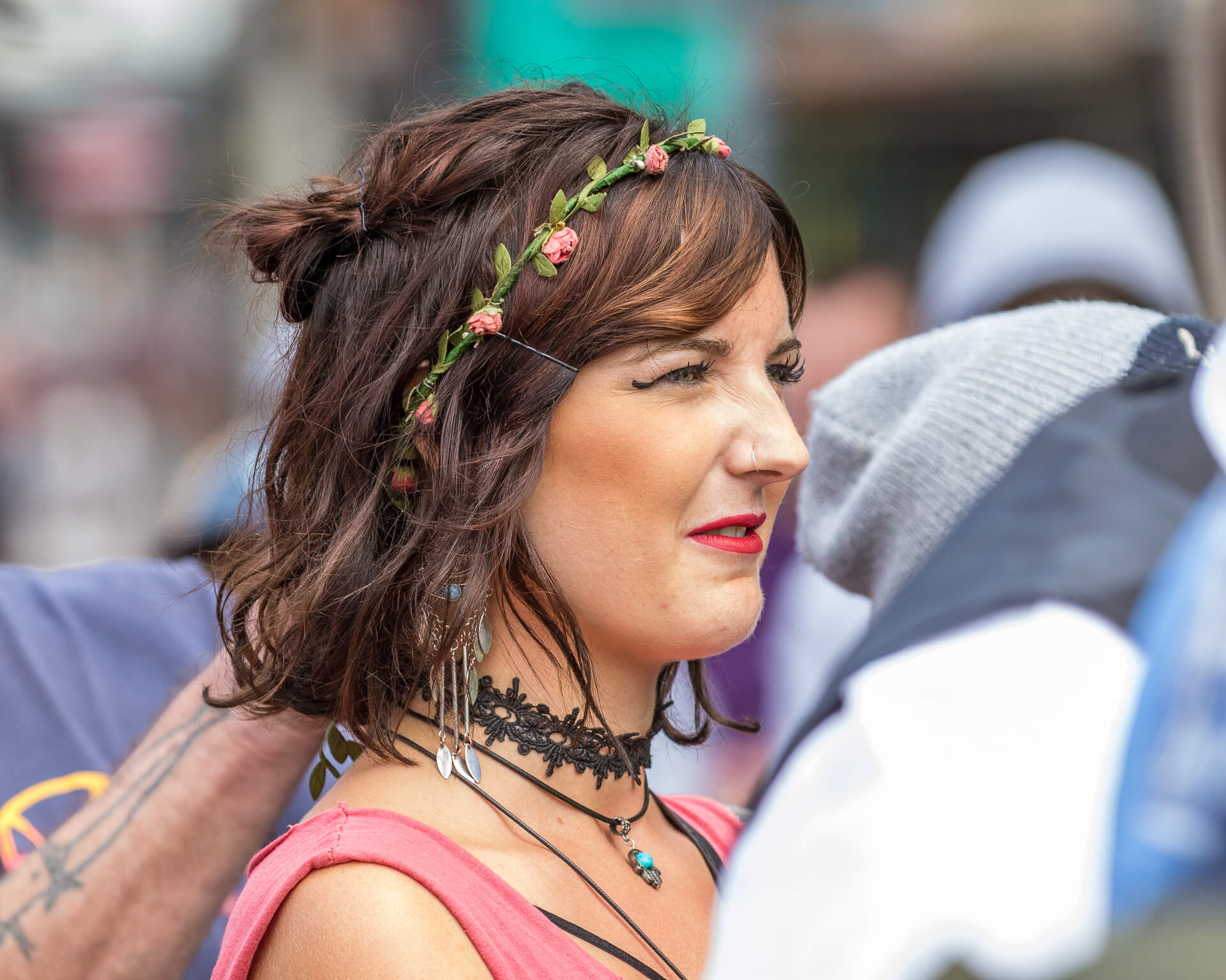 A close up colour head & shoulders image of one of the female marchers on the BNP Marches in Worcester. She wears a decorative choker, bright red lipstick, distinctive eyeliner, and has a small garland of flowers in her hair.