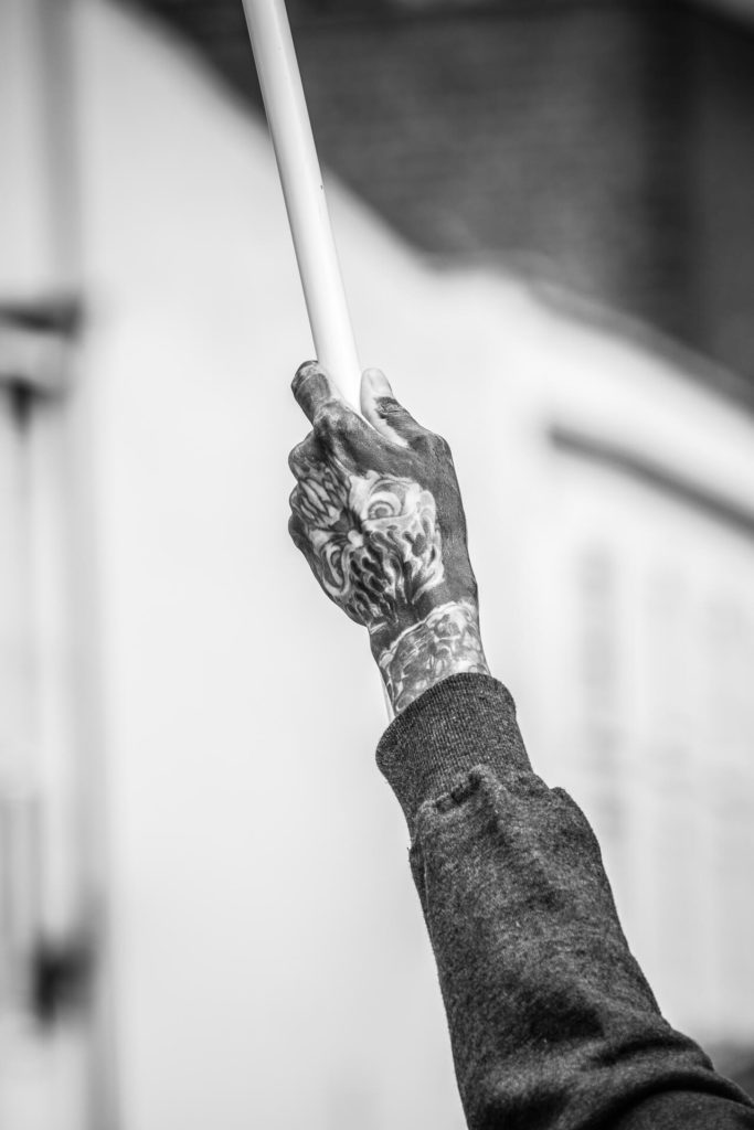 A black & white image, taken from a distance, of the heavily tattooed hand of one of the individuals participating in the BNP Marches in Worcester in 2019. He holds aloft a flag attached to a thin white pole.