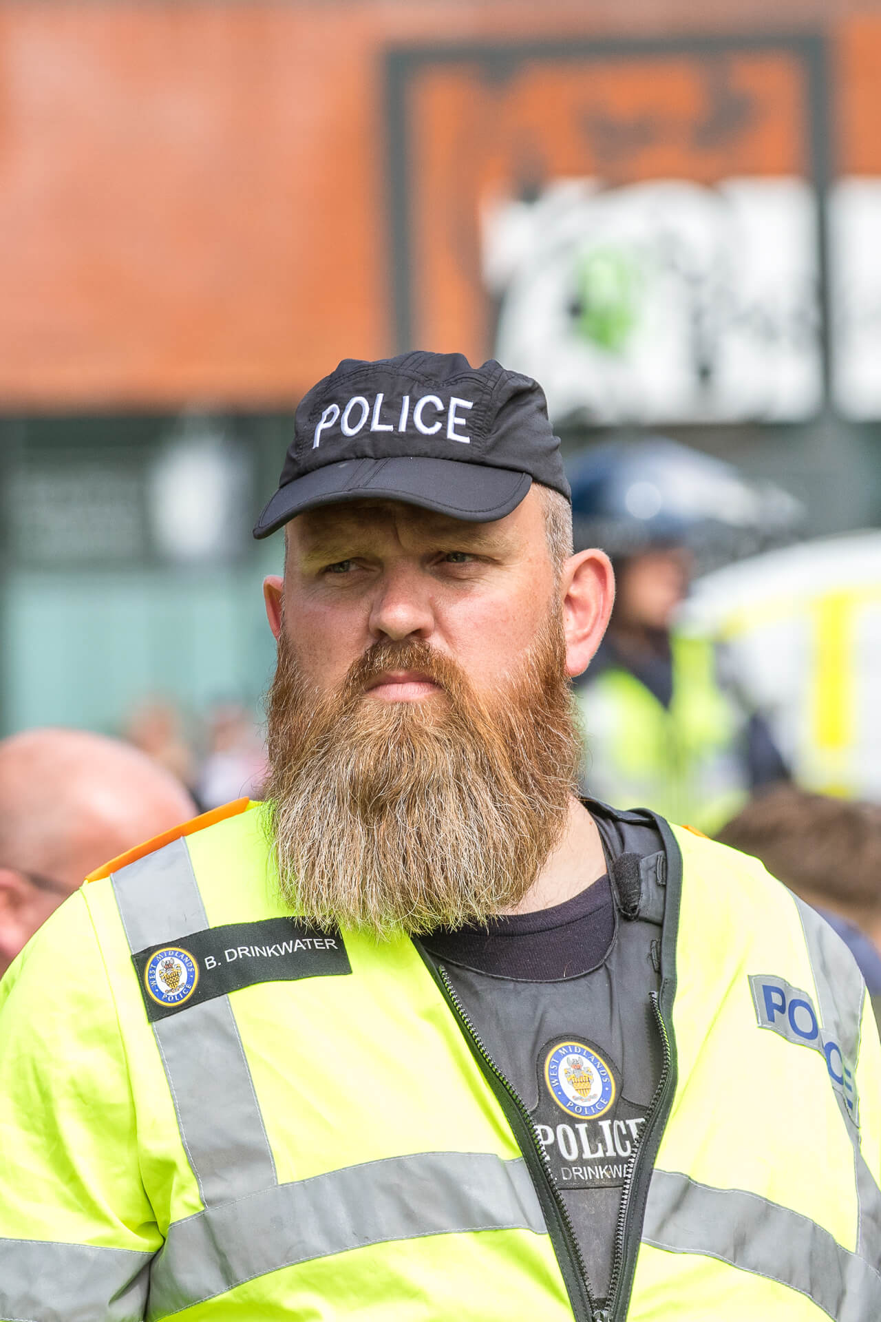 PC Drinkwater of the West Midlands Police seen on duty during the BNP March in Worcester in 2019. PC Drinkwater is looking across and slightly to his right hand side. He is seen in a Hi Viz jacket and black baseball cap (with POLICE written on it), he sports a magnificent full beard and moustache.