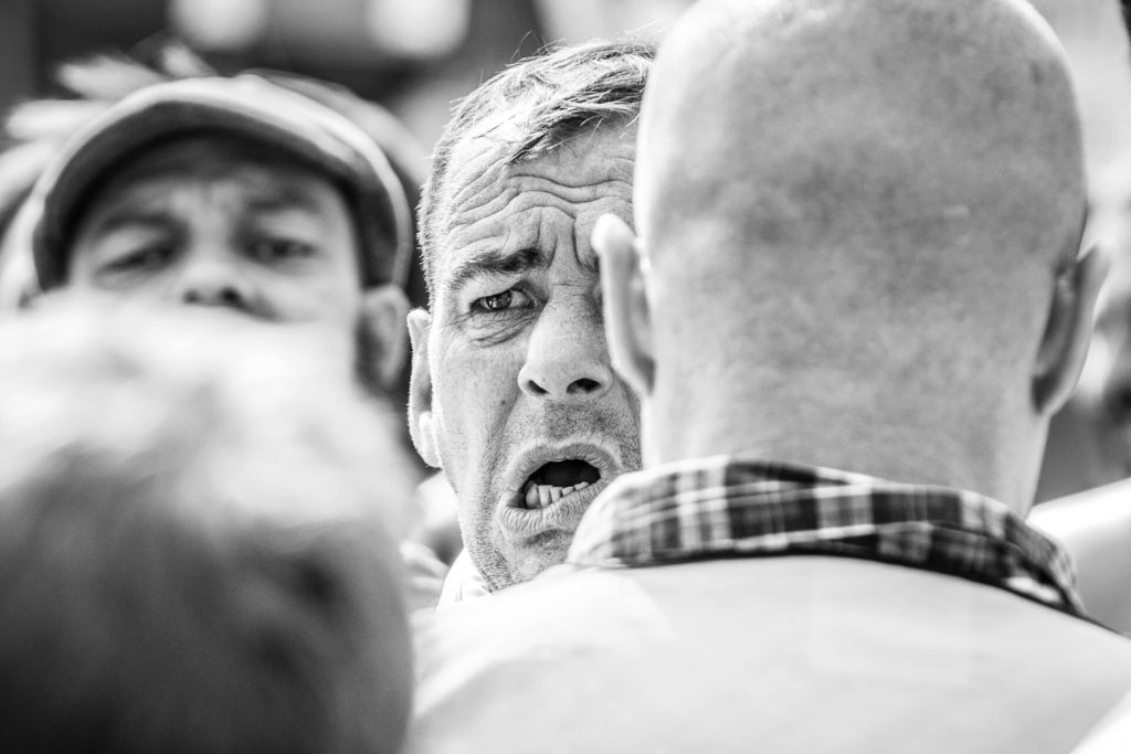 A close up image of the right hand side of the face of a marcher on the BNP March in Worcester. Seen in black and white, he stares straight ahead, he is open mouthed, and has a serious look on his face.