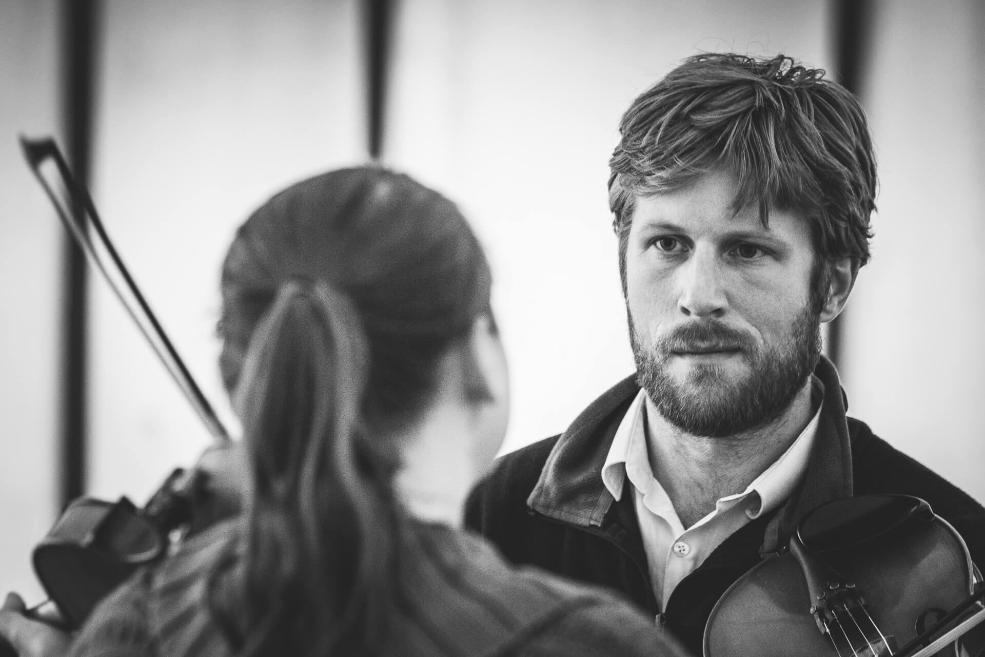 A Black & White head & shoulders image of 2 fiddle players at the Bromyard Folk Festival. The gentleman (who is in focus and facing the camera) stares intently at his female companion (who is out of focus and facing away from the camera). The image suggests a very deep and/or passionate bond between the two.