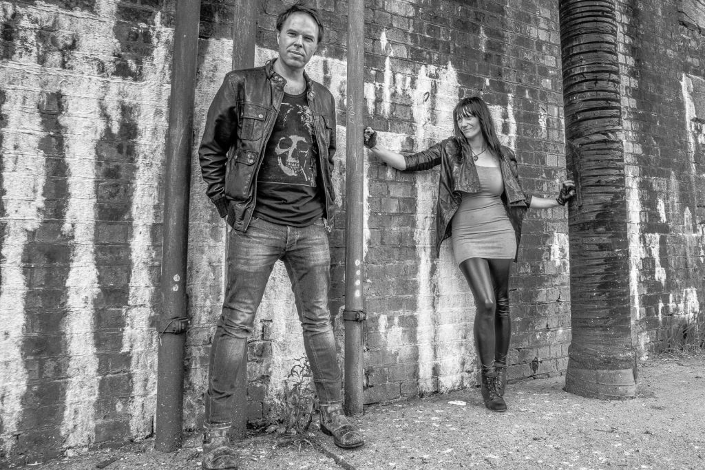 Harlem Dandy (a now defunct) Worcester based duo pose by a brick wall for an image taken as part of a promotional shot for them. In this black & white image Clare (Vocals) stands, arms outstretched, to the right of the image and looks across at Phil (Guitar) who is stood facing the camera, hands in his pockets.