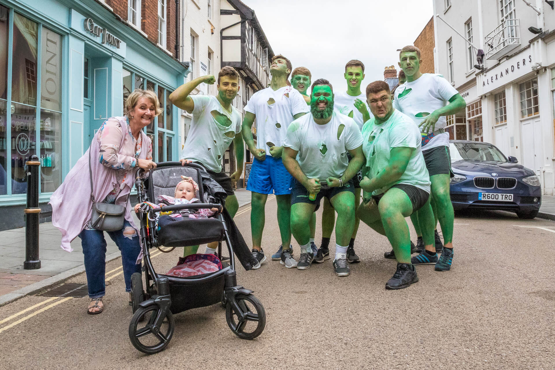 A street image taken during the Worcester Music Festival 2019 of a group of lads from a local rugby club dressed (in ripped/torn shirts and shorts), and made up as, the character Hulk; to add to the image several adopt a 'Hulk' type of pose. On the right hand side of the image (photobombing the scene) is a smiling lady with a baby in a pushchair. Her pose seems to suggest )in a light hearted way) that one of the 'Hulks' could be the childs father!