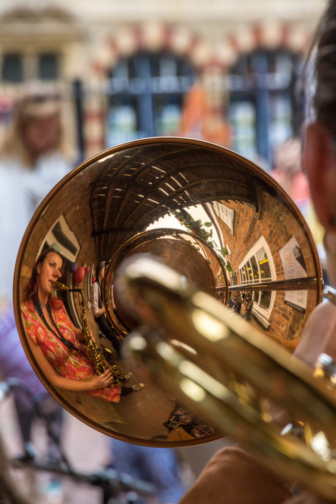 Taken from behind the player and over his left shoulder an alternate view of a trombone as it is being played. In the image you can see the tuning slide, the bell tube, and the bell. Reflected in the bell is a female saxophone player who is part of the group with which the trombone player plays.