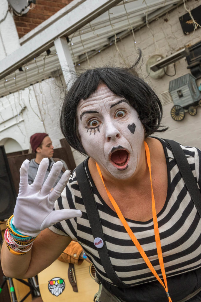 Nicola, one of the street charity collectors for the Worcester Music Festival is seen here in a mime type pose. Open mouthed she has her right hand raised she has a feigned look of surprise on her face. She wears a black and white striped top, white gloves, braces, and her face is made up with white powder, she has a small black heart on her left cheek.