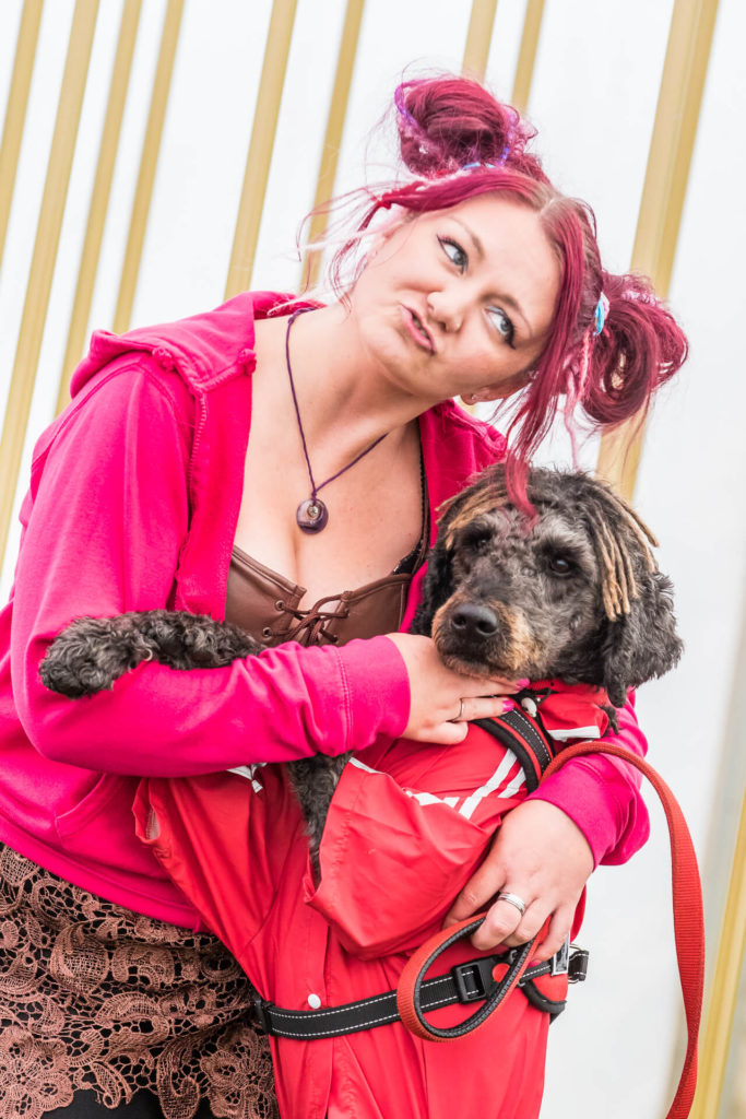 """A colour image of a young lady with pinky red coloured hair as she leans over and cuddles her dog as he stands with his paws on her chest, the image was taken at Dubs of Anarchy 2018. Her hair is in pigtails, her dog has short curly fur giving an impression of """"dogs and their owners""""."""