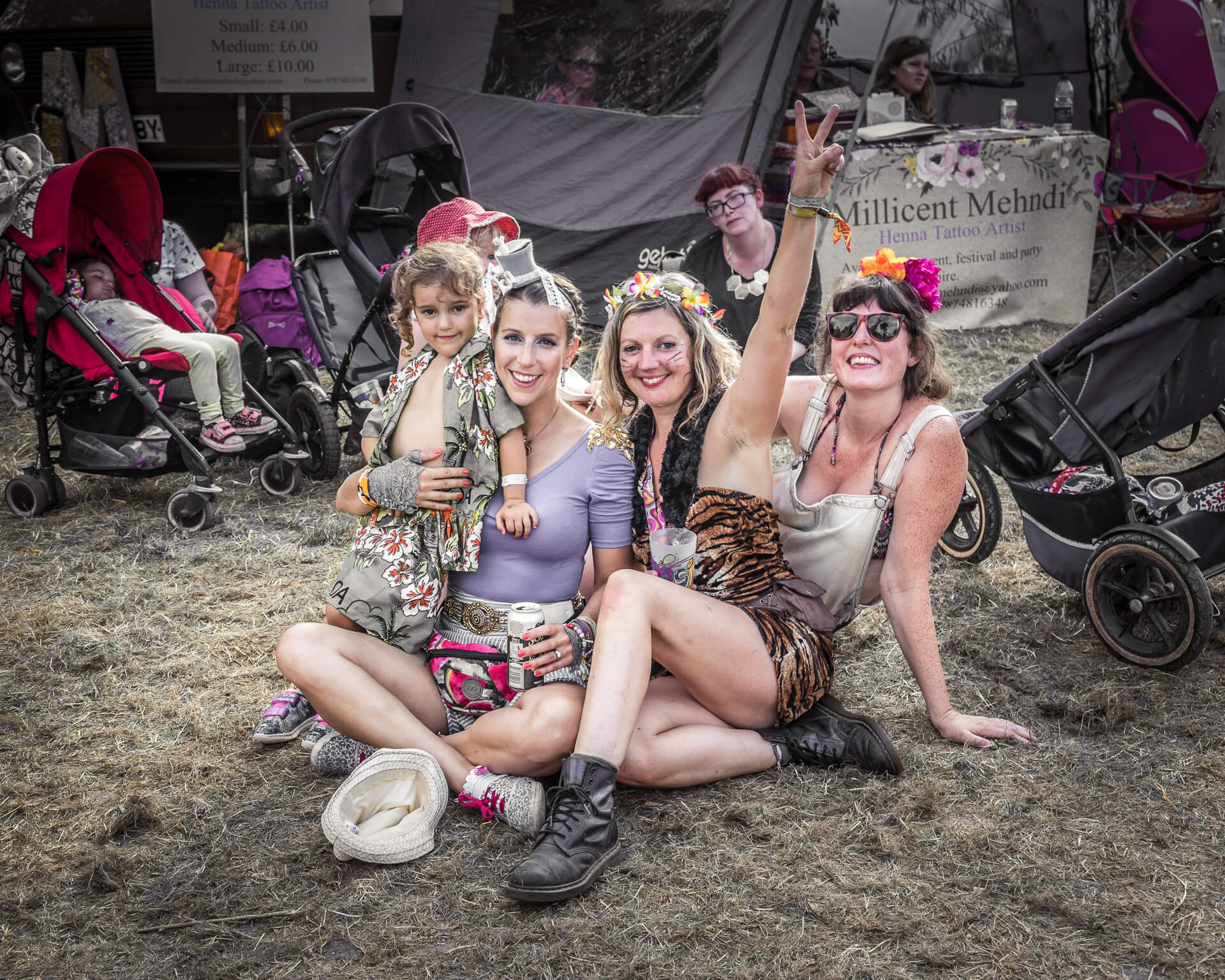 A subdued colour image of 3 female friends sat together, along with the young daughter of one of them, on the ground in front of the henna tattoo parlour at Nozstock in 2018. They all smiley broadly for the camera as one raises her left arm making a 'Peace' sign.