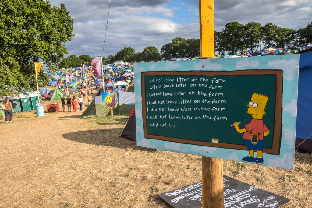 """A sign at the Nozstock festival (which is held in Herefordshire) which shows a Bart Simpson cartoon type character writing on a blackboard. He appears to have written 6 lines of """"I will not leave litter on the farm"""", a not so subtle reminder to festival goers to not drop their litter."""