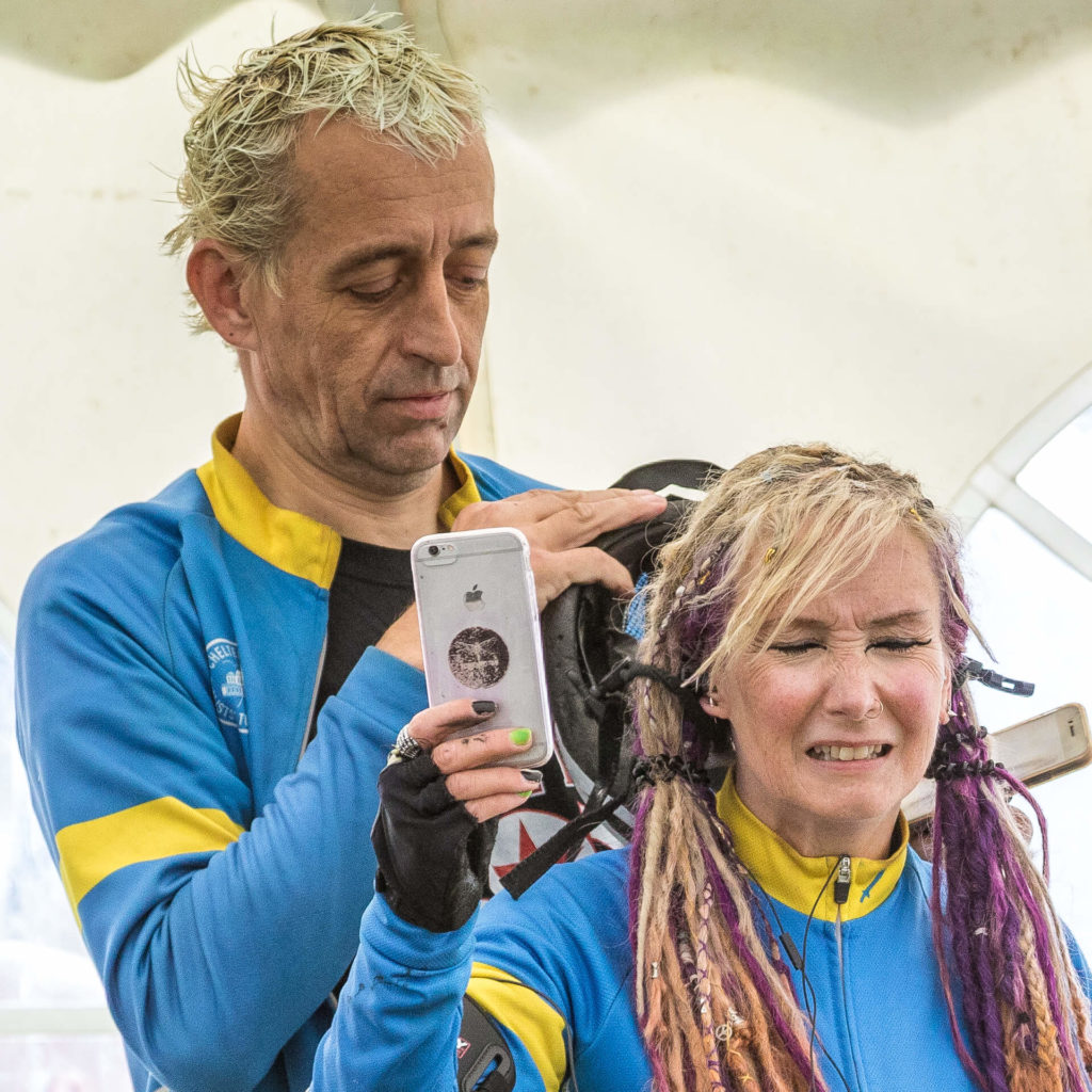 A head and shoulders colour image of a couple who are stood one in front of the other as the man stands behind his partner trying to untangle her semi dreadlocked multicoloured hair from her cycle helmet. She grimaces as he does. She holds her mobile phone up presumably with the camera operating trying to see what he is doing!