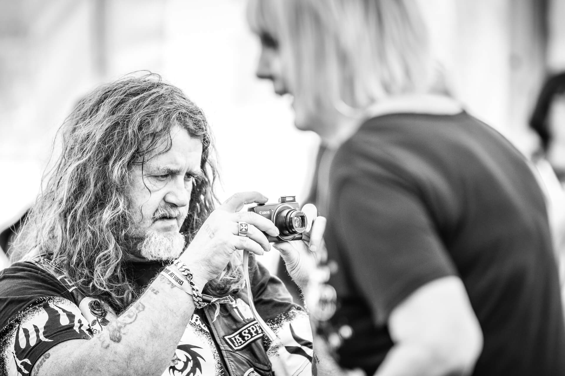 A head & chest image, in black & white of a long haired male festival goer at Dubs of Anarchy Festival. He appears to be concentrating on the view through the viewfinder of a small Canon Compact camera.