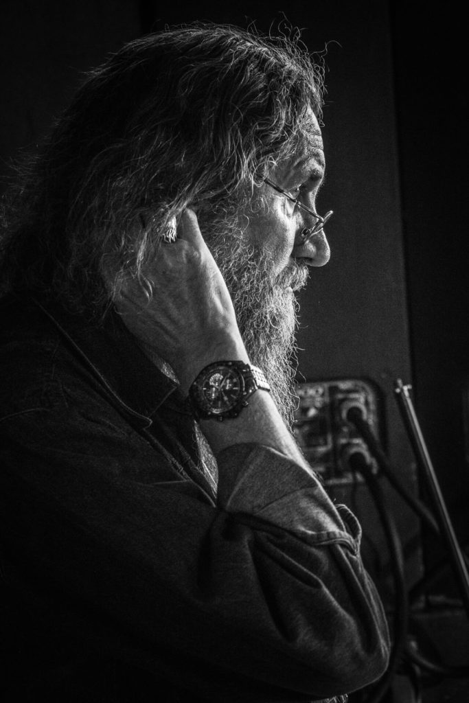 A side on, chest upwards black and white image of 'Krusher' as he sits watching at the side of the stage at the Drunken Monkey Rock Festival. The man is a legend in Heavy Metal circles having been responsible for some classic album cover designs.