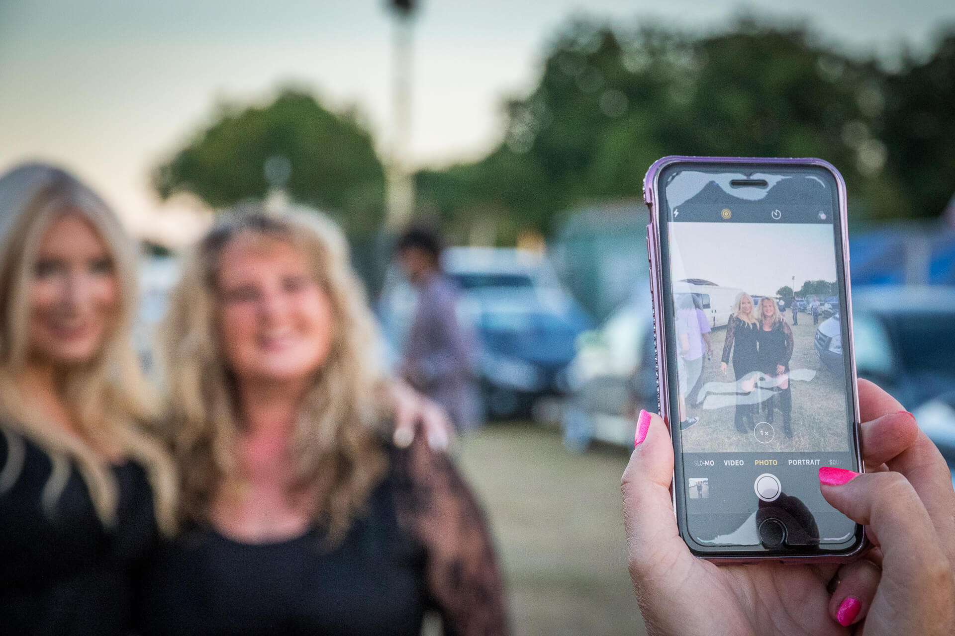 An image of a mobile screen as someone (with bright pink fingernails) takes a shot of two blonde female performers as they wait to go on stage. In the colour image the smiling pair are in focus on the screen of the mobile whilst they are out of focus in this image.
