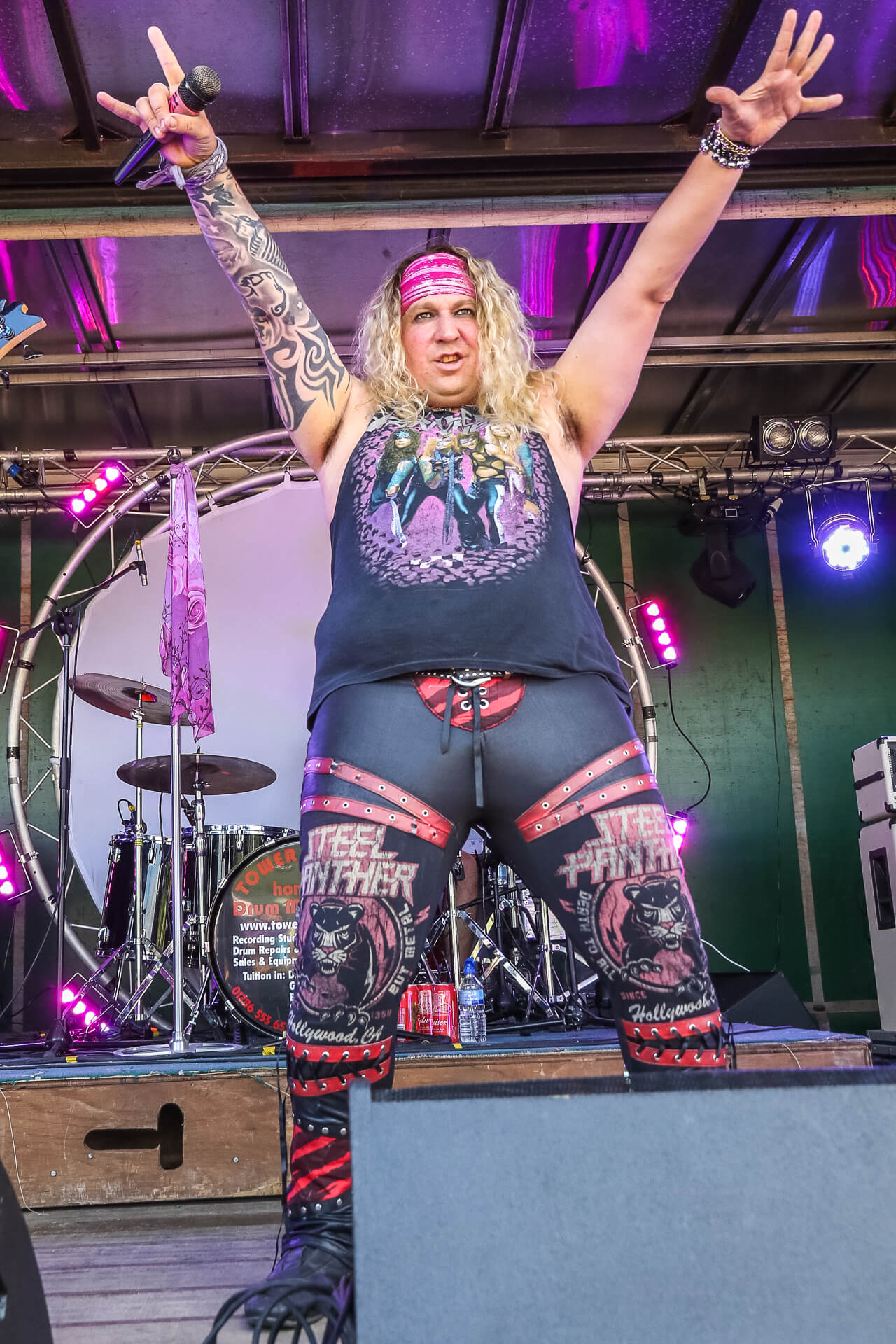 Jamie, frontman of Steel Panther tribute band Surreal Panther, stands on stage arms aloft taking the crowds applause and adulation at the end of the bands set. His alter ego is Michael Starr the Steel Panther frontman. Jamie who is seen in colour holds the mic in his right hand whist making a 'Horns' gesture.