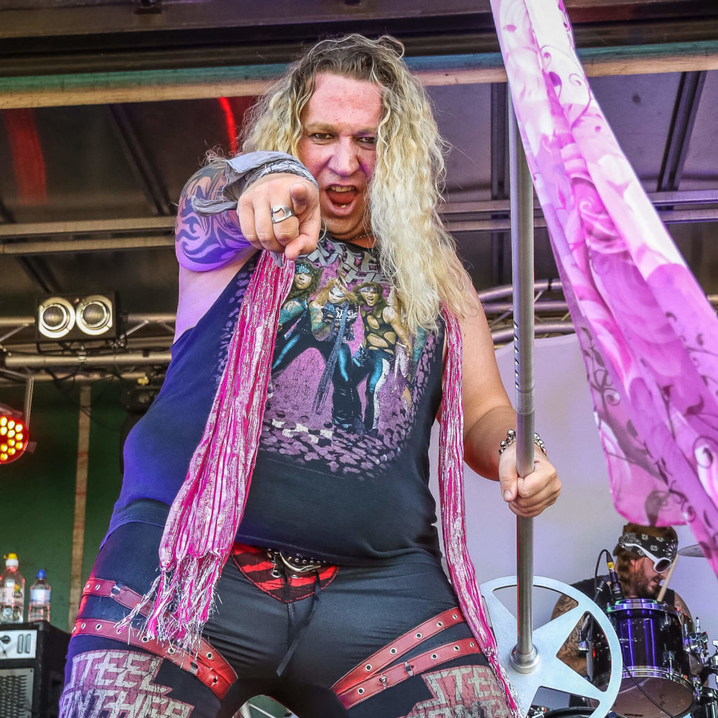 Jamie, frontman of Steel Panther tribute band Surreal Panther points at the camera whilst performing on stage. His alter ego is Michael Starr the Steel Panther frontman. Jamie who is seen in colour from the knees up points with his right hand and in his left he carries his scarf adorned mic stand.