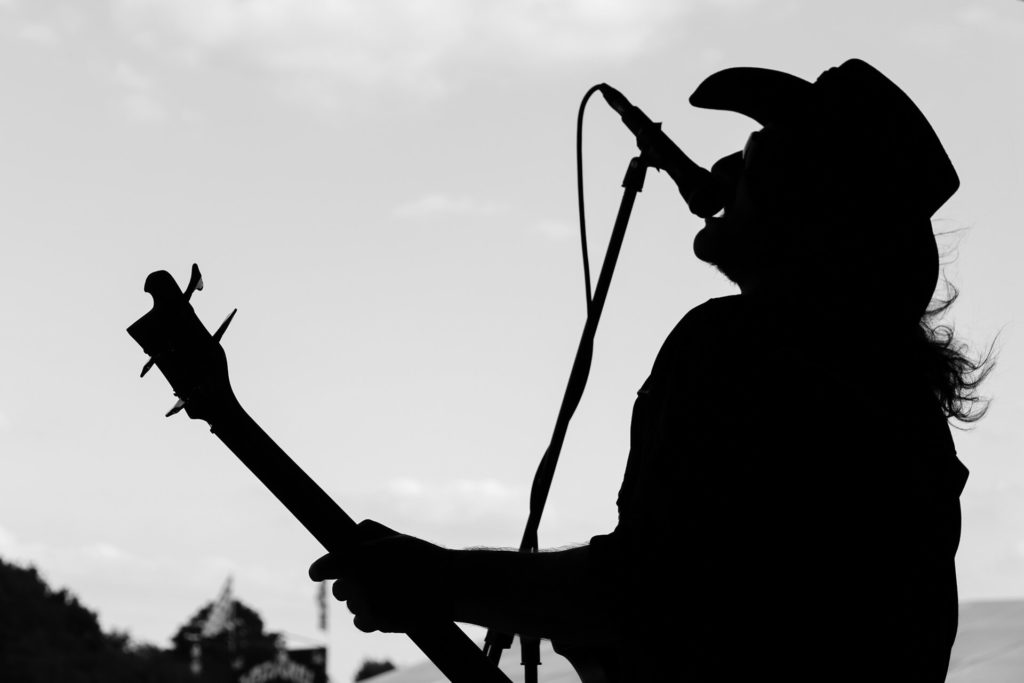 A waist up black & white image of Rob Campbell, a 'Lemmy' lookalike as he performs on stage at The Drunken Monkey Rock Festival in 2019 with the band Motorheadache. Stetson wearing Rob is seen in this image in silhouette in a typical Lemmy pose, head back and mouth close to the mic.