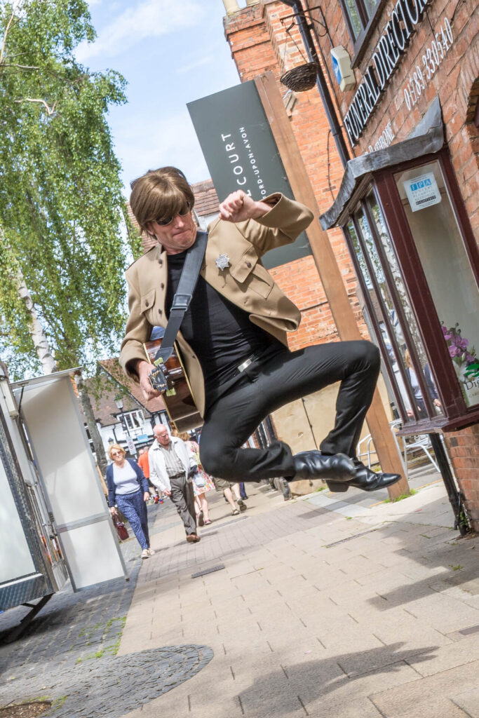 A coloured image of Gaz, a John Lennon impersonator, in stage dress and carrying his guitar, as he jumps into the air and taps his heels together as he walks down the street in Stratford Upon Avon as part of a promotion drive for his stage show.