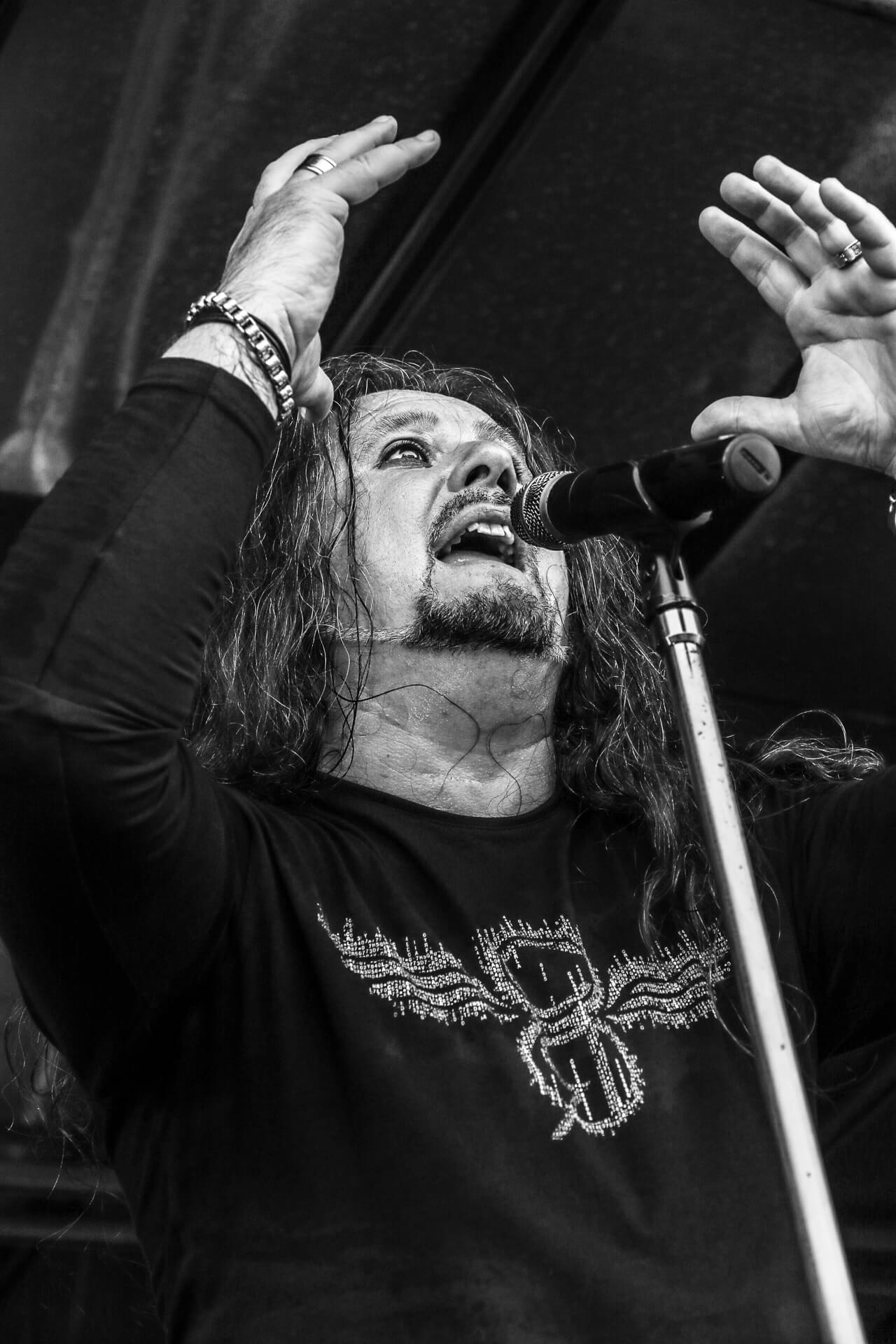 Tony Peacock, frontman of Sabbotage, a Black Sabbath tribute band seen on stage at The Drunken Monkey Rock Festival in 2019 with the band. Tony is seen in this image arms raised up near his head as he sings into the mic.