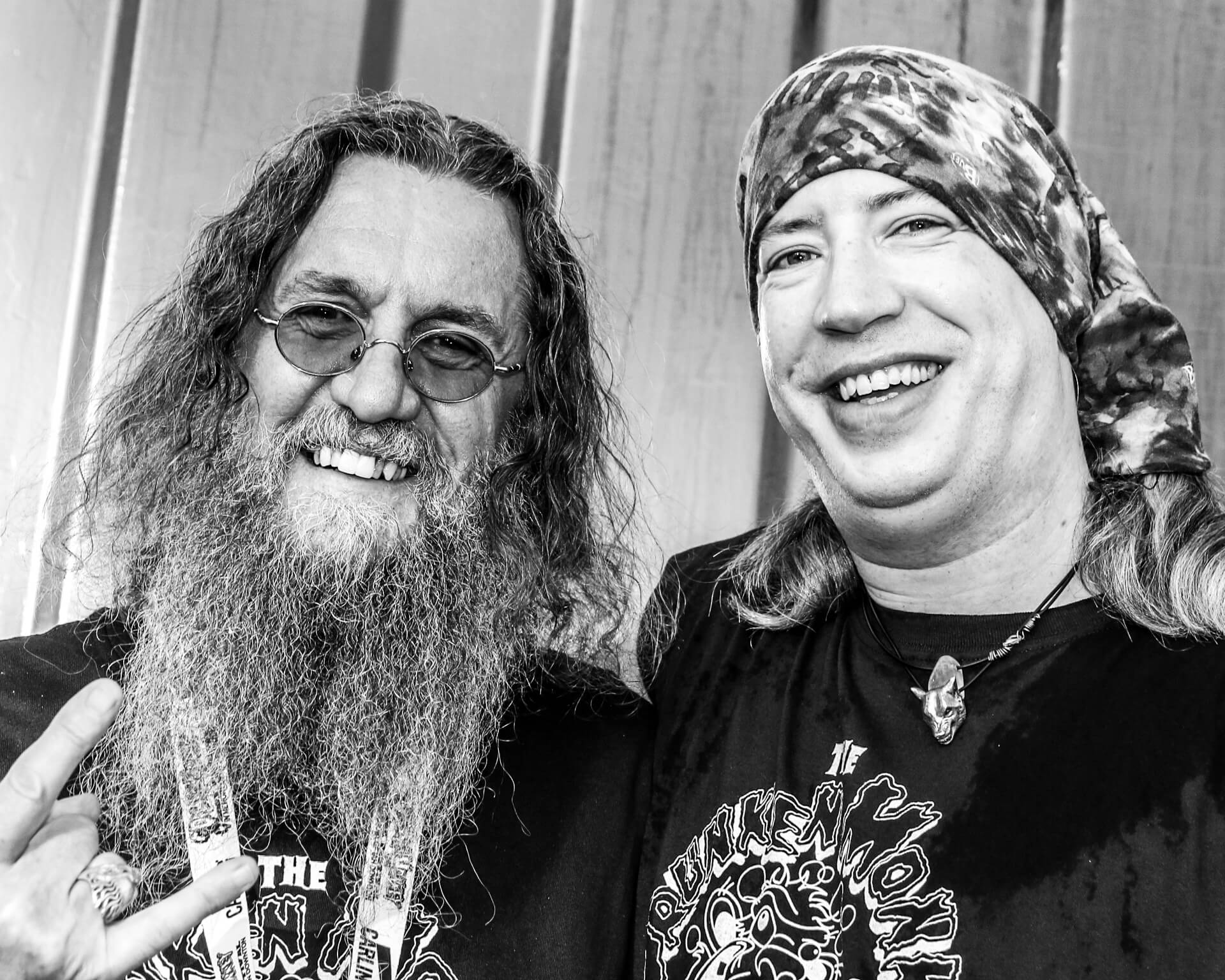 Paul, the then Bassist with Sabbotage, seen here in a chest up black & white image at the Drunken Monkey Rock Festival stood back stage alongside Krusher. Krusher is a life long hero of the bandana wearing Paul and this was an opportunity not to be missed. Both smile broadly for the camera and Krusher gives the universal 'Horns' gesture with his right hand.