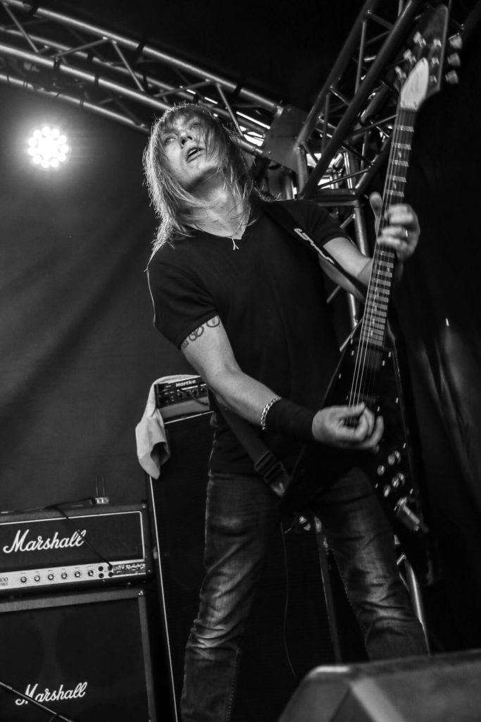 A 3/4 length black & white image of a member of Burnt Out Wreck as he plays guitar on stage at The Drunken Monkey Rock Festival 2018.