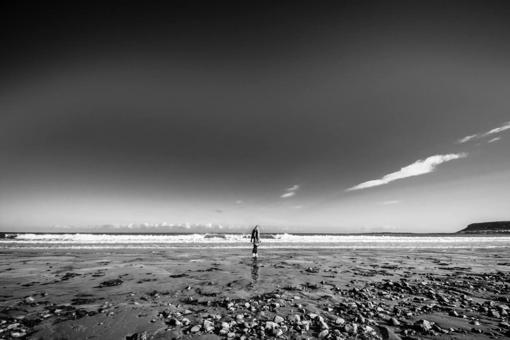 Seen all alone (in black and white) on a deserted beach walking barefoot in the receding water, with rollers crashing in just behind her, is Sara as she contemplates her life.