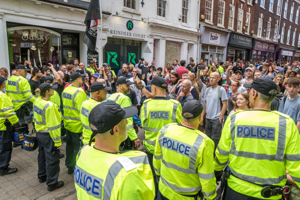 A colour image of part of the police lines as they prepare for the BNP March in Worcester. The Police Officers all wear black baseball caps and Hi Viz jackets as they face the already growing crowd in a pedestrian area in Worcester.