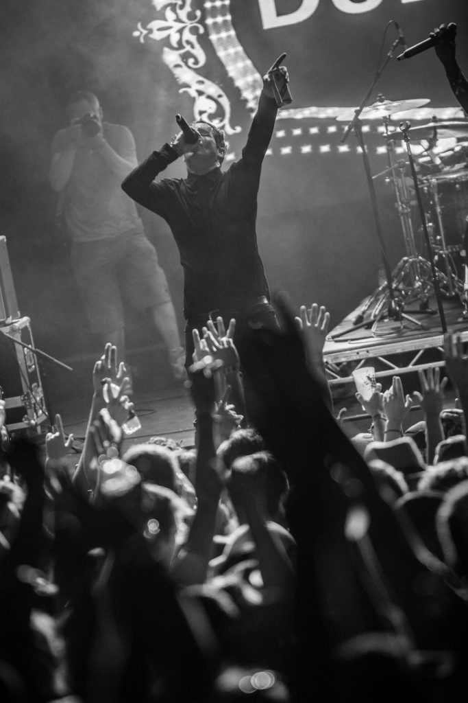 Seen from the back of the arena and across the top of the crowd an onstage image of Barry, frontman of the Dub Pistols. Barry is seen dressed completely in black clothing, stood legs apart, in his right he holds the mic as he sings, his left arm is raised upwards, and in it he holds a can of lager. The blurred arms of members of the crowd can be seen raised in the foreground of the image.