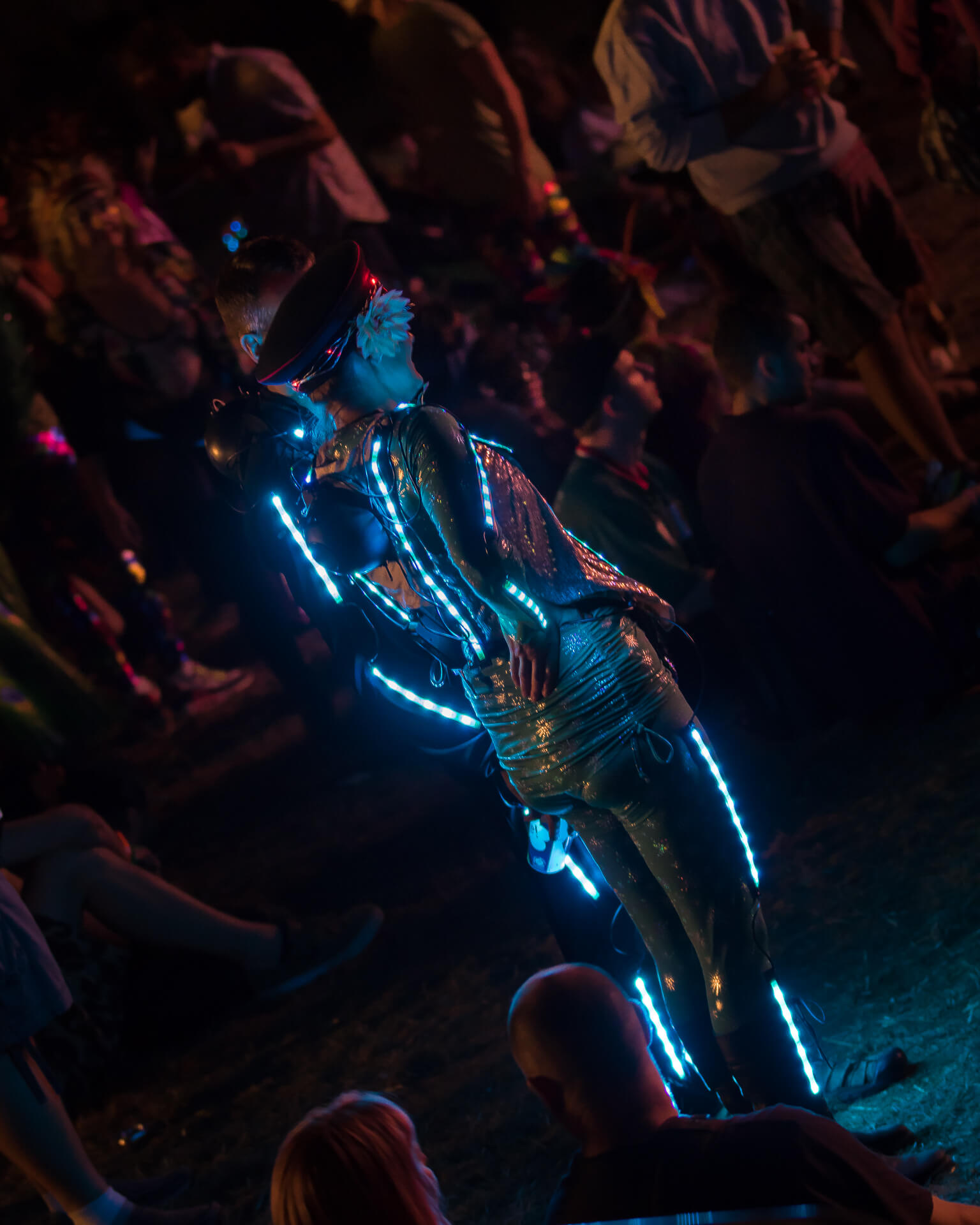 A full length body image of two festival goers in the main arena at Nozstock as they watch proceedings. Taken at night the pair wear outfits with lights sewn into them so as they appear illuminated. The crowd have given them room so they stand out.