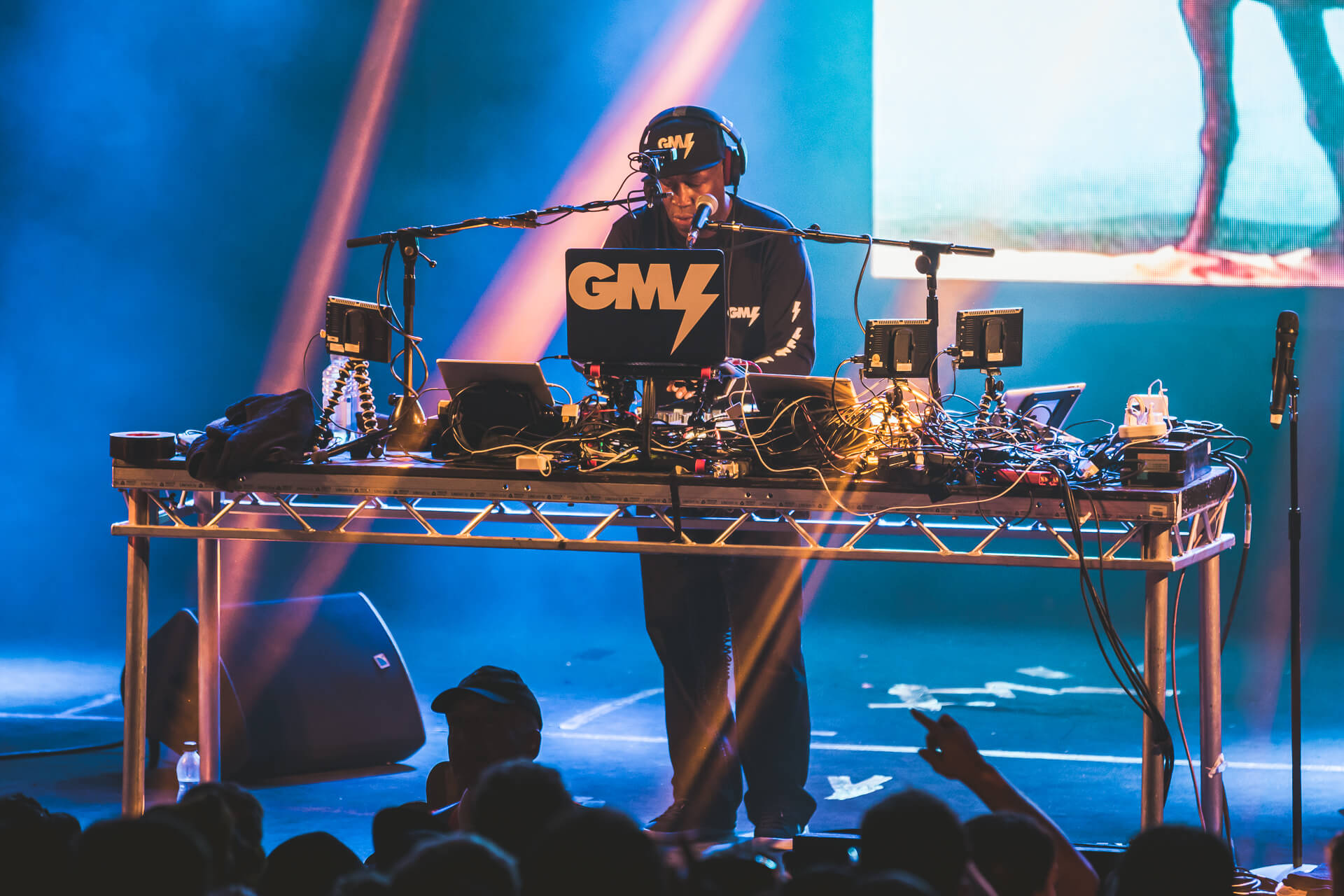 A colour image of Grand Master Flash seen here on stage at Nozstock in 2018, he is stood behind his mixing equipment as he performs for the raucous crowd.